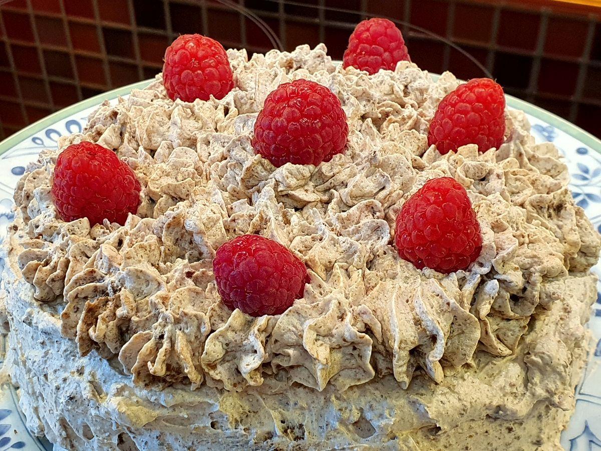 Schokoladen-Mandeln-Sahne-Torte mit Himbeeren garniert
