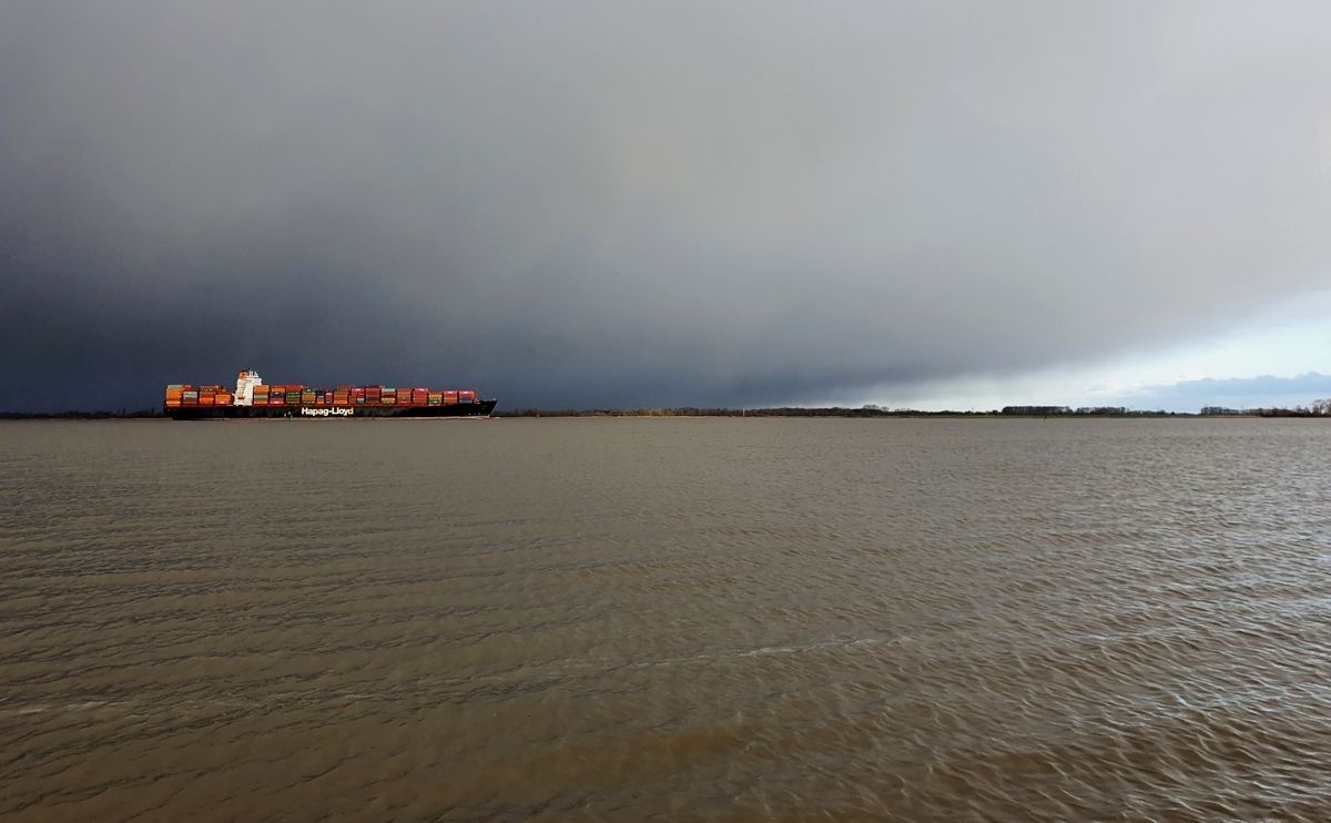 Containerschiff auf der Elbe Höhe Stade auf dem Weg nach Hamburg vor einem winterlichen Regenschauer