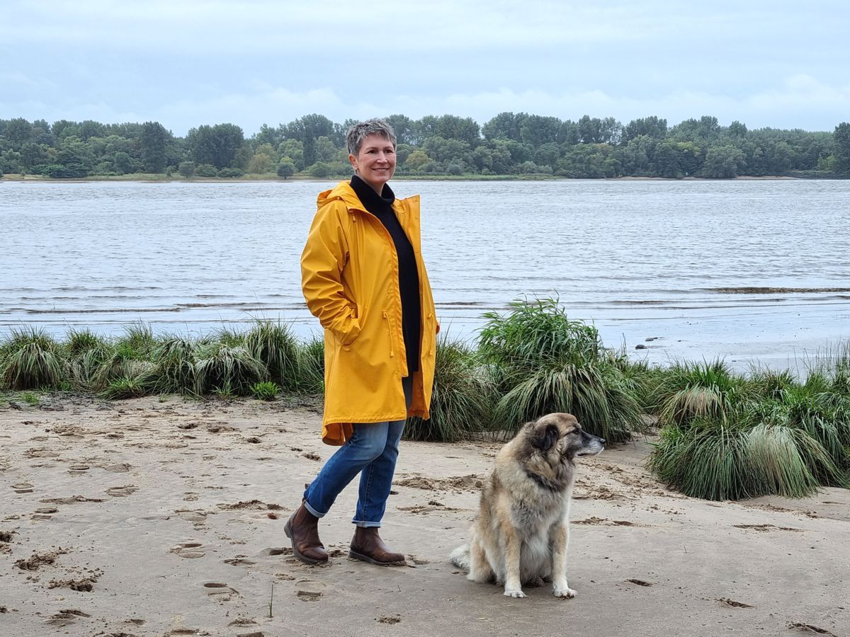 Ines Meyrose – Outfit 2021 – Rollkragenpullover dunkelblau, Jeans blau, Chelseaboots braun, Regenjacke gelb - Ü50 Bloggerin mit Hund Paul